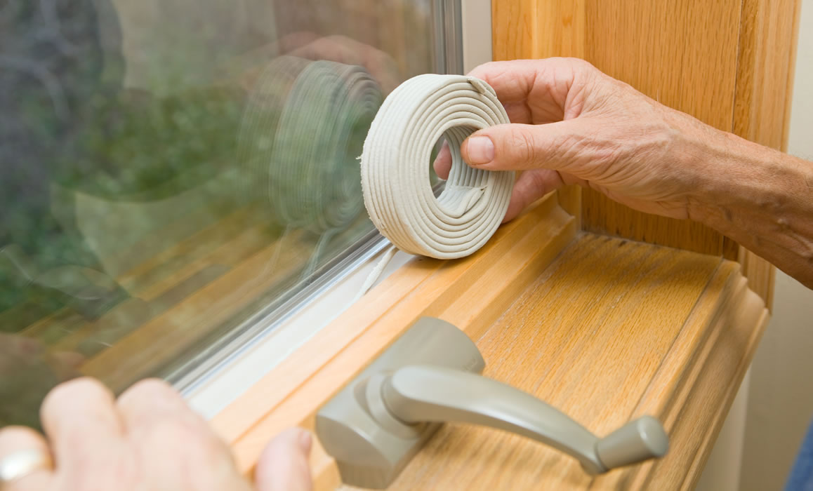 hands applying weather stripping to window