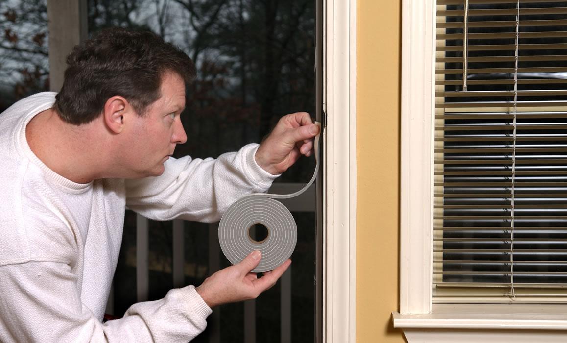 hands applying weather stripping to doorframe